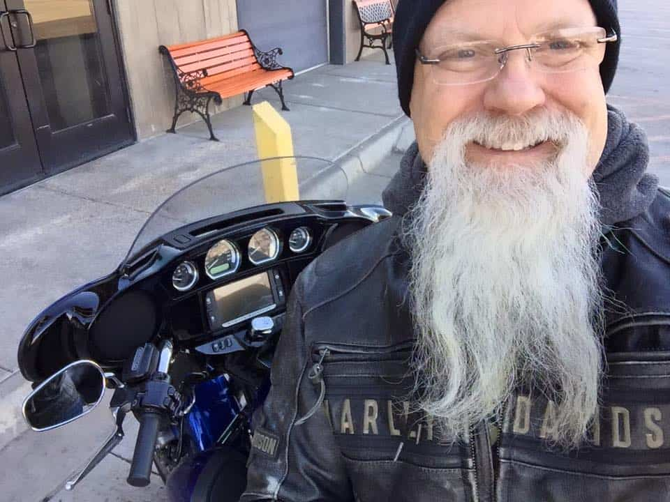 Randy posing with his motorcycle with long beard