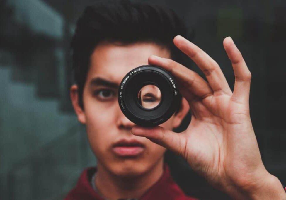 A man looking through a camera lens that shows his head upside down.