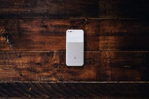 A white and gray phone laying face down on a brown wood surface.