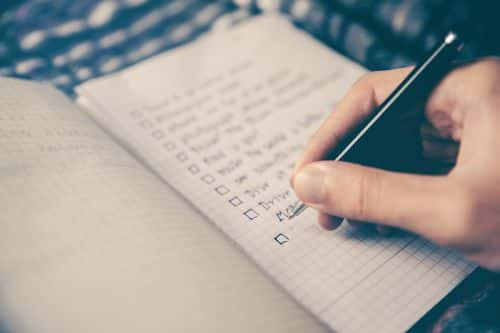A checklist being made in a notebook.