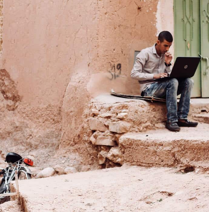 Young man working on his laptop in the middle of a dusty and eroded street.