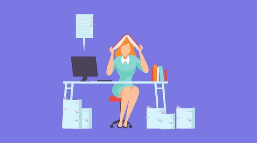 overwhelmed woman at desk with paperwork