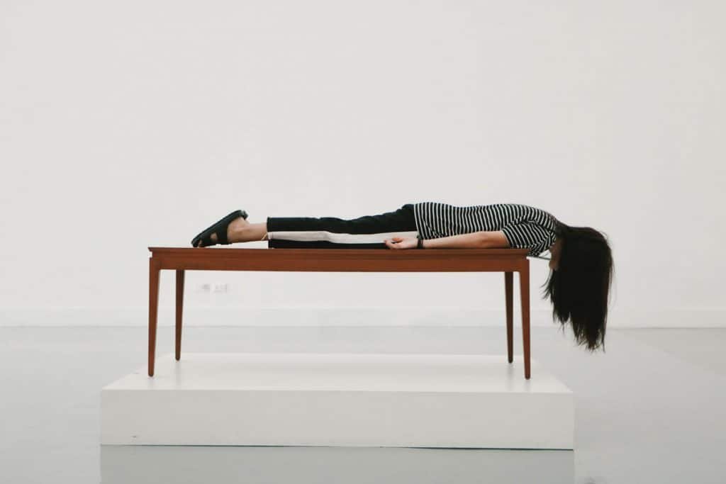 Young lady looks defeated laying face down on a table.